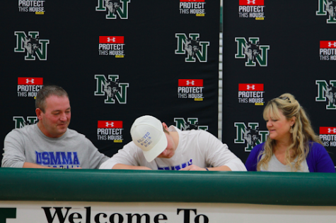 Senior Bo Kemmet signs for college as his mom and dad smile