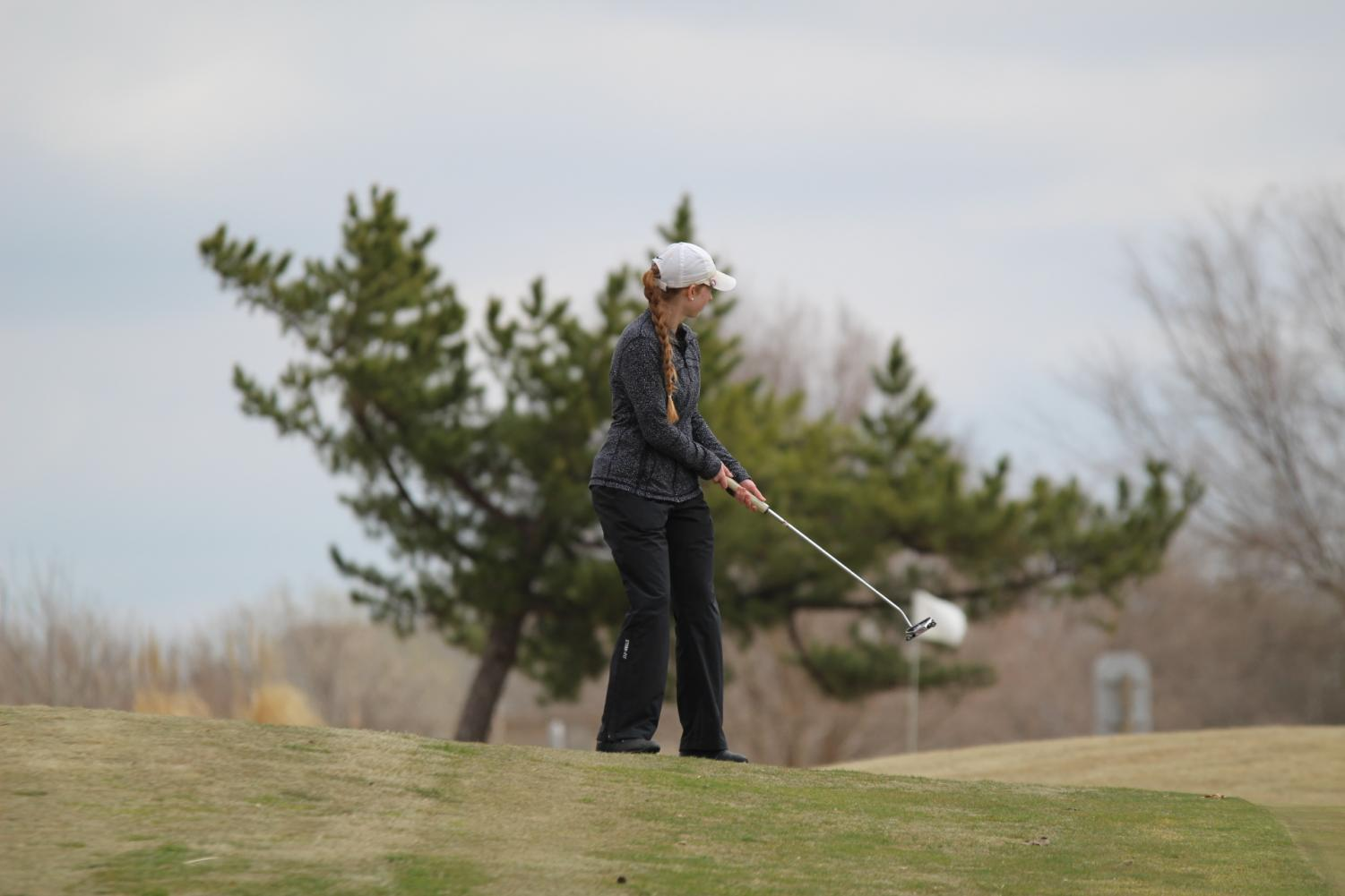 Kenli Divelbiss hits her ball onto the green around hole seven.