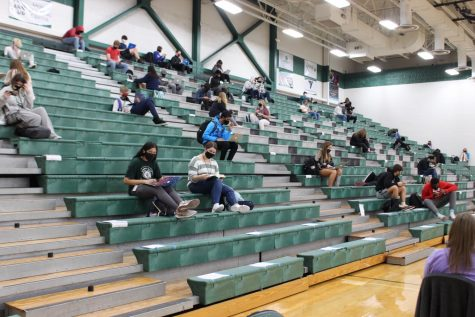 Students sitting on the left side of the gym during 3rd hour while the freshmen are taking the PSAT