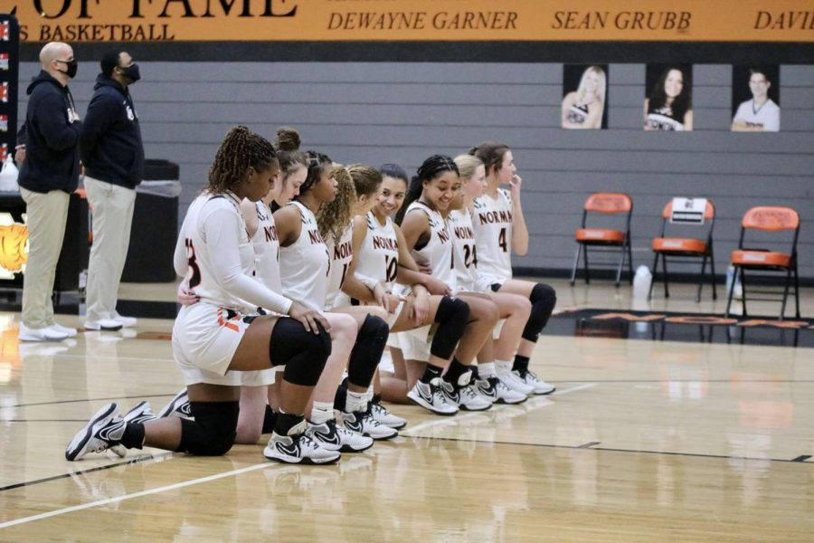 The Norman High girl's basketball team kneels for the National Anthem.