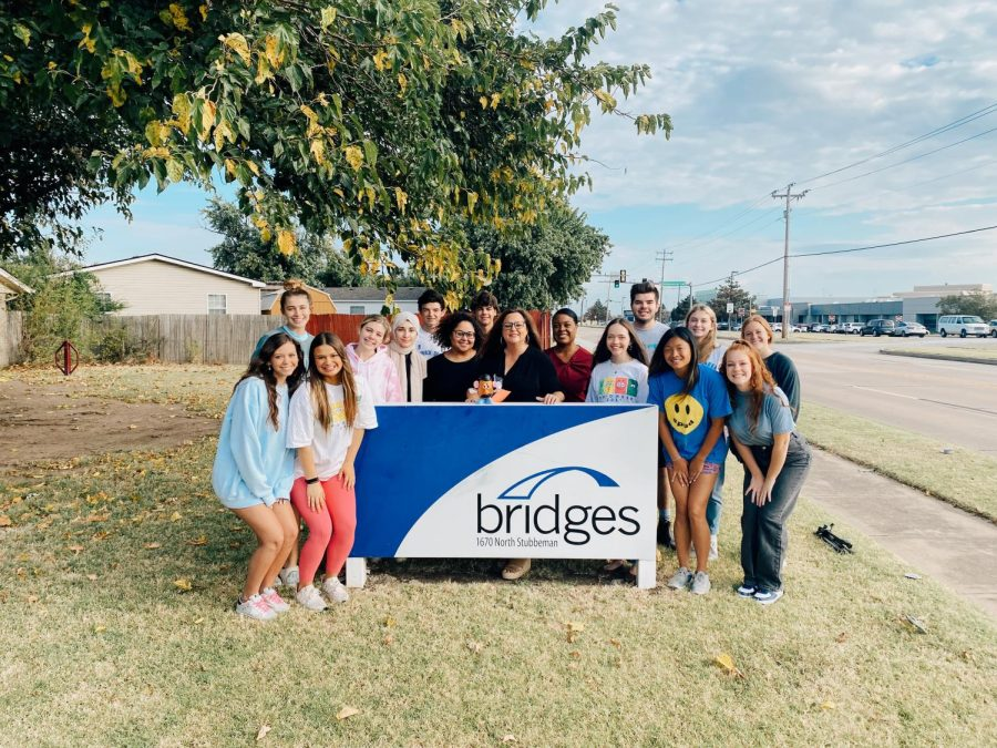 Students involved with SPUD posing in front of the Bridges sign.